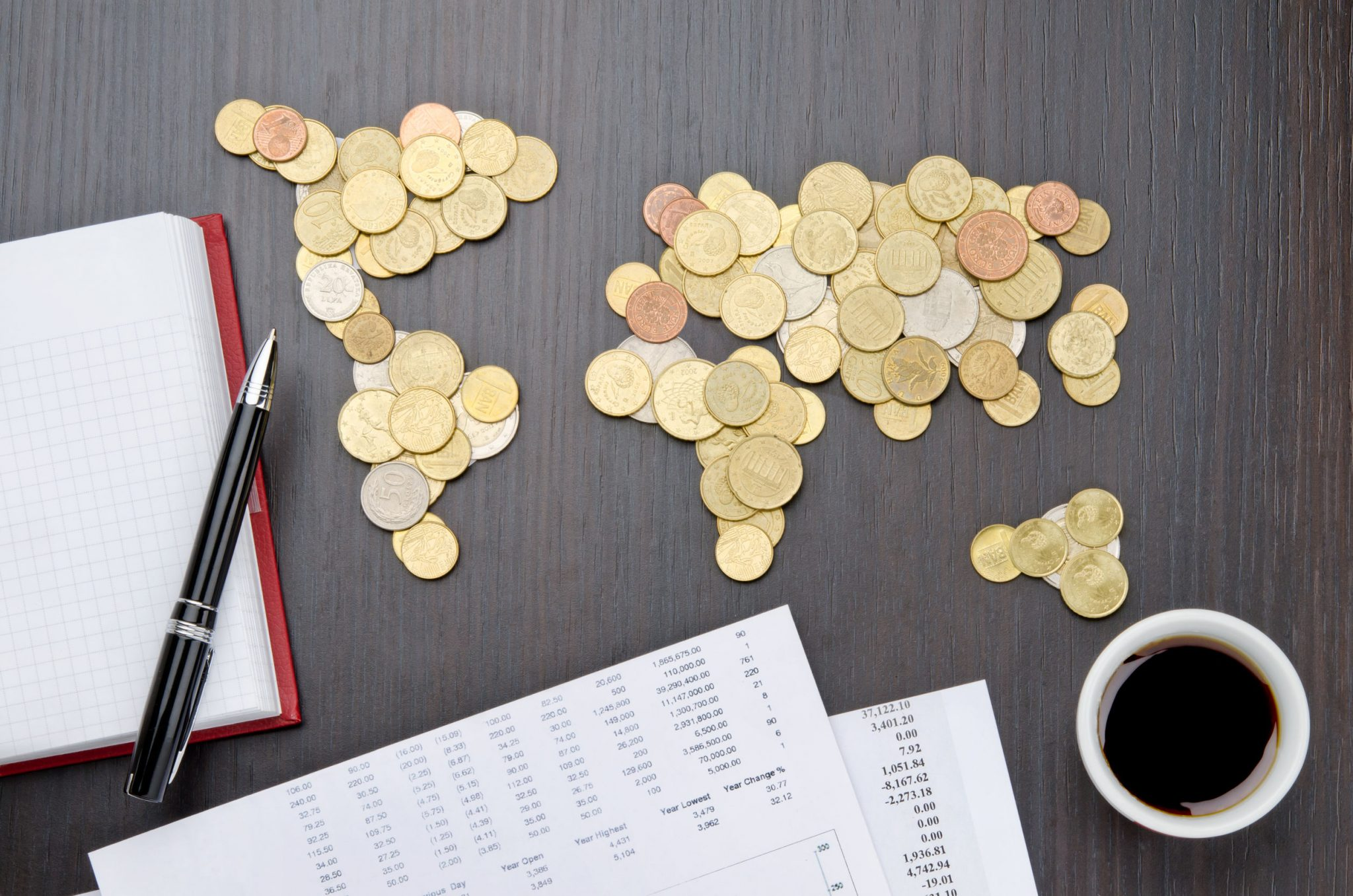 coins in the shape of world countries on a table with financial reports