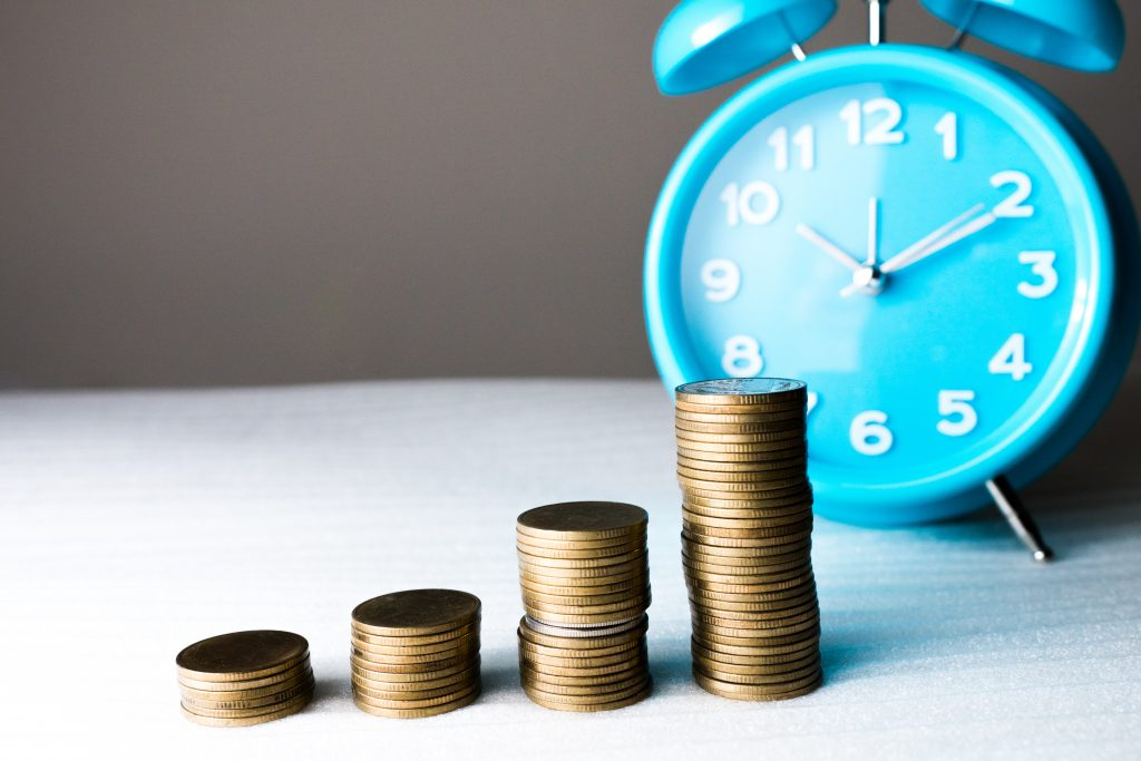 coins in a stairstep with blue clock in the background